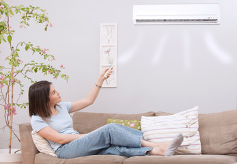 woman using remote control of air conditioner