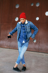 Cool latin man wearing denim clothes dancing on the street.