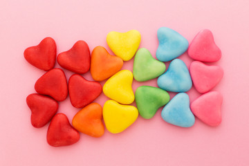 Multi-colored heart-shaped candy arranged in rainbow colors, on a pink background