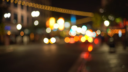 Blurry background plate of city traffic at night with bokeh headlights passing