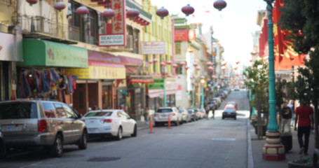 Defocused background of Chinatown district with Chinese lanterns and tourists