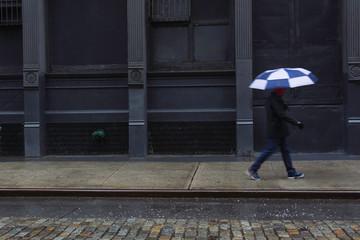 Man with umbrella walking along street through winter sleet storm