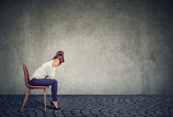 Businesswoman in depression sitting on chair