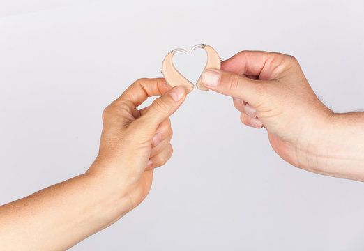 Woman's and man's hand forming a heart shape together with hearing aids