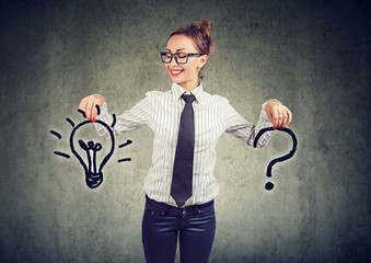 Happy young business woman with question and an answer idea light bulb