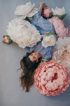 Daydreaming girl with long hair posing with big paper flowers of delicate colors