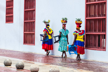 Fototapeten Südamerikanisches Land Traditional fruit street vendors in Cartagena de Indias called Palenqueras walking in front of the building of the town hall of Cartagena