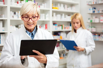 Happy mature female pharmacist using a tablet. Young female colleague standing behind and writing data to a clipboard Pharmaceutics and healthcare.
