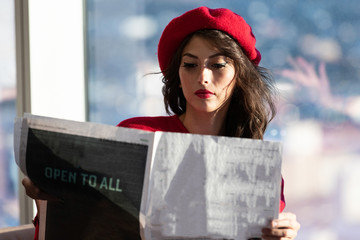 French woman wearing red beret reading the newspaper