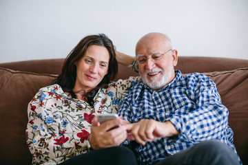 Father and his daughter using phone at home.