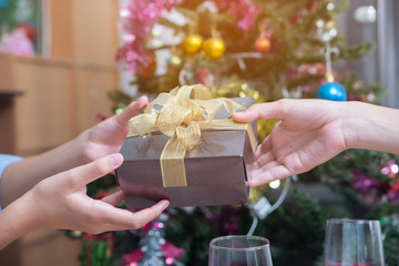 New Year and christmas's surprise gifts concept.Hands of Young Man give a gift box (with gold ribbon)to happy girlfriend,he wants a surprise on New Year and christmas's Day.