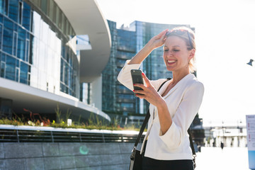 Blonde businesswoman using a phone in the city