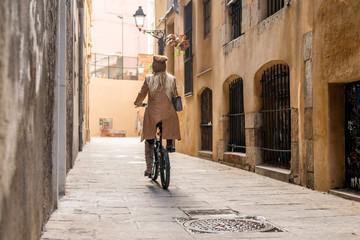 Woman cycling on bike along narrow street.