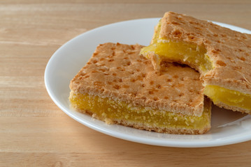 Close side view of two freshly baked lemon squares with one bitten on a white plate atop a wood table.