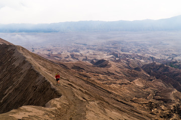 A young woman hiking on the edge of a volcano crater