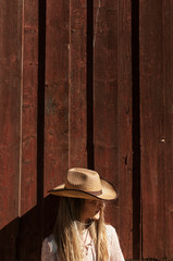 Young woman in cowboy hat on wood