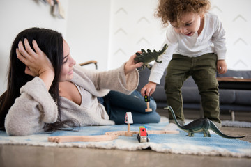 Mother playing dinosaurs with toddler son