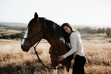 Girl hugging brown mustang
