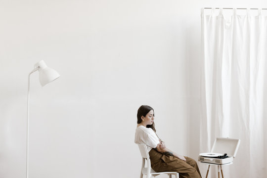 young woman sitting in big white room listening to a vinyl music record