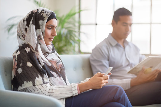 Woman in headscarf using mobile smartphone indoors