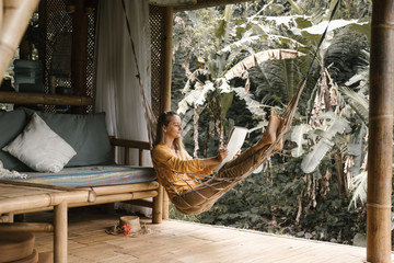 yong women, painter lie in the hammock in the bamboo cozy house in the jungle