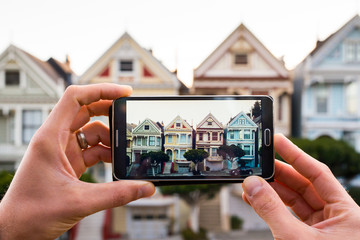 Man uses smartphone to photograph homes on a San Francisco hill