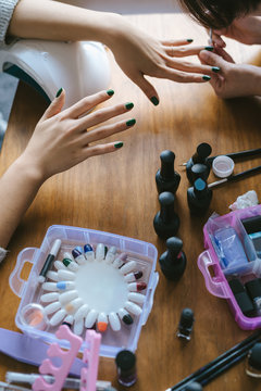 Girls applying nail polish to friend
