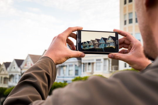 Man uses a smartphone to photograph a row of homes in San Franci