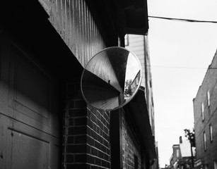 Abstract view of a traffic mirror in a tight alleyway