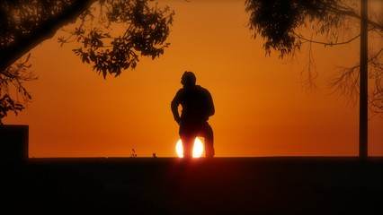man with hand on hip and setting sun below his legs