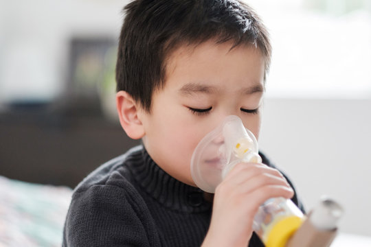 Asian Kid Using Asthma Inhaler Medication
