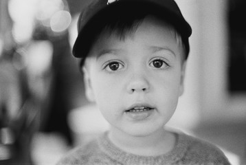 Black and white portrait of a cute young boy wearing a hat