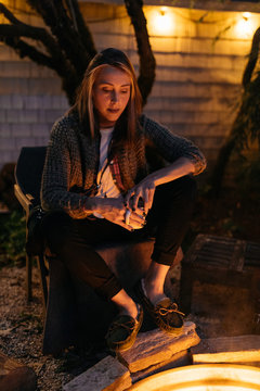 Young female sits next to warm fire in evening on summer fall night