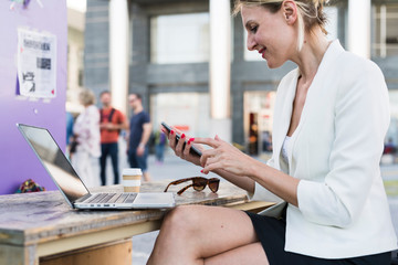 Businesswoman working in the city using technology