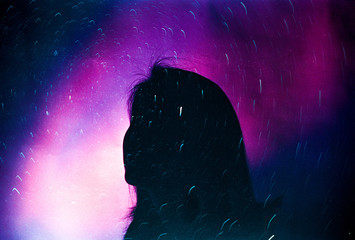 Silhouette of woman looking up at the night sky filled with stars