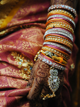 Colorful bracelets and hand with henna tattoo