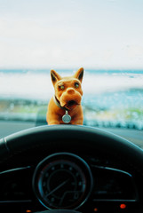 Vintage Bobble Dog on car dashboard with scenic ocean view in ba