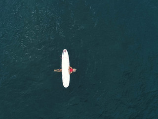 Top view: girl relaxing with surfboard at waves