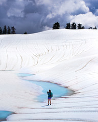 A female photographer standing in front of a bright blue alpine lake thawing in the spring