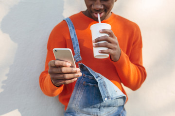 Closeup portrait of a cool black man using his phone outdoors.