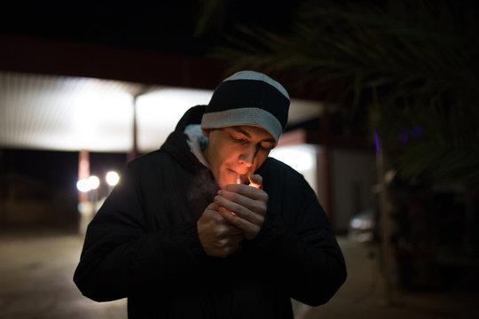 Man lighting cigarette on dark street