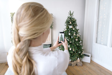 Woman taking shot of decorated Christmas tree