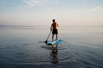 Man using stand up paddle in the sea during Summertime