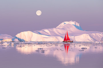 Little red sailboat cruising among floating icebergs in Disko Bay glacier during midnight sun season of polar summer. Ilulissat, Greenland. Wall mural