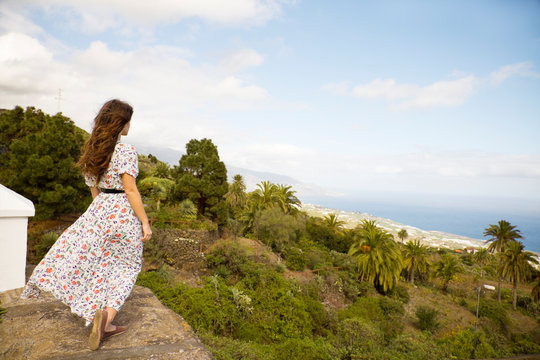 Brunette young woman in long dress looking at view