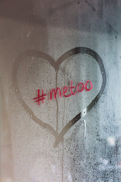 #metoo written in red lipstick on a steamed up glass showerwall with a heart shape drawn around it.