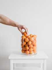 Hand taking orange from jar