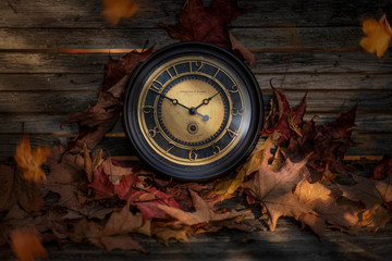 Vintage clock and autumn leaves on wood background