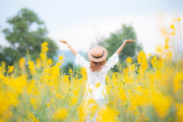 Asian young woman enjoy and stretching her arms with sky background in nature yellow flower farm, her is feeling relaxed and happy in the sunset; Relax and happy concept.