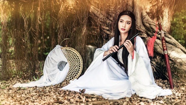 Beautiful Chinese woman with a traditional suit with a flute in her hands, Beautiful and belligerent face, Young woman with a samurai bushido